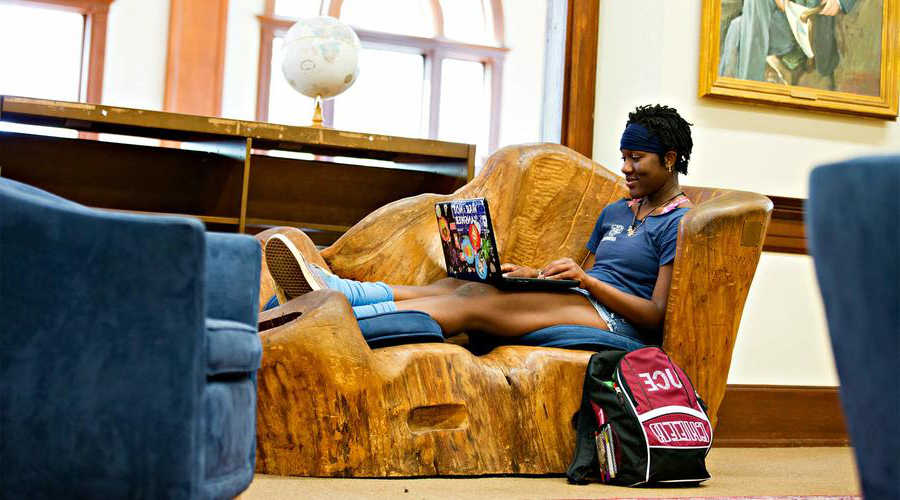 A student sits in a hand-carved wood chair in Hege Library.
